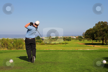 Golfer #62 stock photo, A golfer playing golf on a green.  Movement on golf club and ball in the air. by Sean Nel