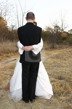 Wedding #12 stock photo, Bridal couple standing on a dirt road in an embrace by Sean Nel