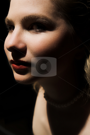 High contrast portrait of a nude woman stock photo, A very high contrast image of the face of a nude woman (breast just visible in bottom corner) She has blonde hair and very deep red lips by Sean Nel