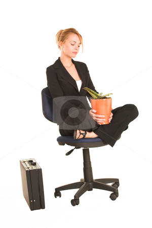 Businesswoman #263 stock photo, Blonde business lady in formal black suit. Sitting on an office chair with pot plant on her lap.  Looking down by Sean Nel