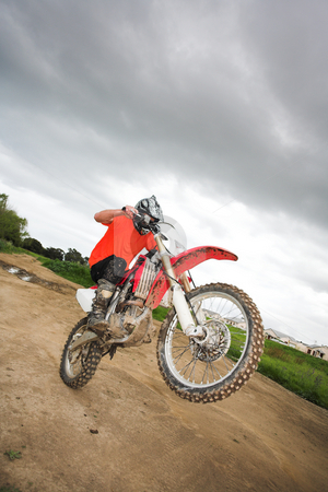 Fun on the motocross bike stock photo, Young man riding around on his dirtbike doing tricks and getting dirty. Movement on edges of motorbike by Sean Nel