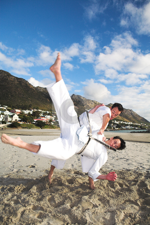 Men practicing Karate on the beach stock photo, Young adult men with black belt practicing fighting on the beach on a sunny day - Movement on extremeties of fighters by Sean Nel