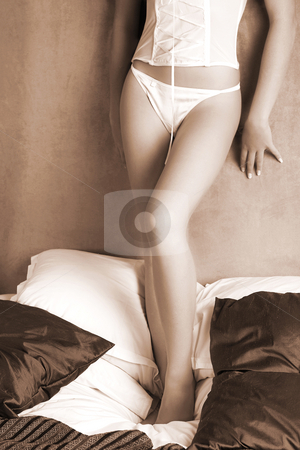 Lingerie#255 stock photo, Woman in underwear standing on a bed. by Sean Nel