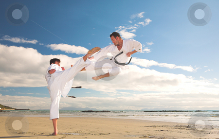 Men practicing Karate on the beach stock photo, Young adult men practicing Karate on the beach. One is in a high kick and the other flying through the air (some movement on the edges) by Sean Nel