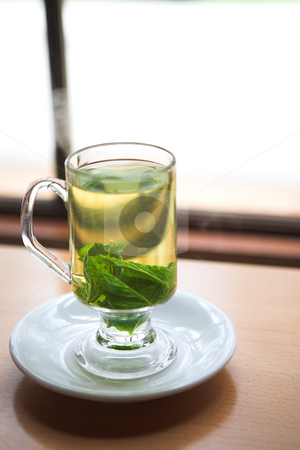 Green mint tea stock photo, Hot green mint tea standing next to a window with whole mint leaves (shallow Depth of Field) by Sean Nel