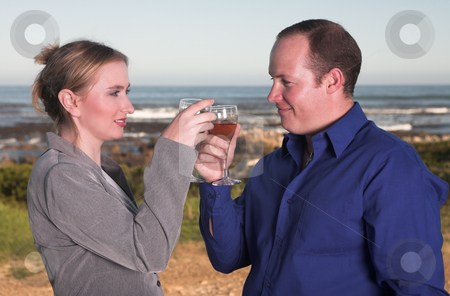 Couple drinking wine stock photo, Young adult Caucasian couple drinking wine outdoor next to the ocean by Sean Nel