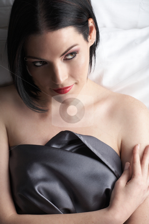 Nude adult woman stock photo, Sensual naked young Black haired adult Caucasian woman, wrapped in a charcoal colored satin, silk sheet on a bed in her bedroom. High contrast lighting. by Sean Nel