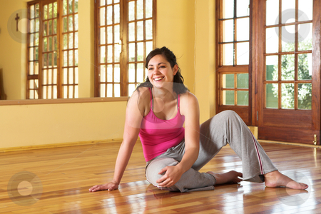 Healthy young woman in gym outfit sitting on the floor stock photo, Healthy young smiling woman with dark hair sitting on the wooden floor in her exercise studio. Resting after yoga stretches associated with health and wellness, as well as general fitness and dieting. by Sean Nel