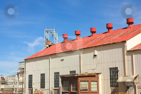 Industrial type warehouse and factory stock photo, Corrugated iron building with red roof on mine premises with shaft winch in the background. Blue sky and sunny day by Sean Nel