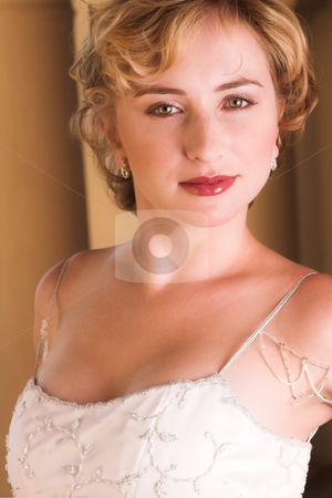 Young blonde bride wearing wedding gown stock photo, Young blonde bride with champagne colored wedding gown and red lips. She is looking over her shoulder with an alluring and seductive look in her green eyes. She is in a luxurious bedroom by Sean Nel