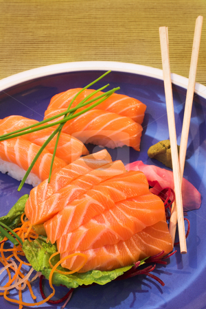 Fresh sushi, sashimi and nigiri salmon on a plate stock photo, Fresh strips of Norwegian salmon Nigiri and rice Sashimi on a blue plate with a bamboo mat in the background and wooden chopsticks on the plate by Sean Nel