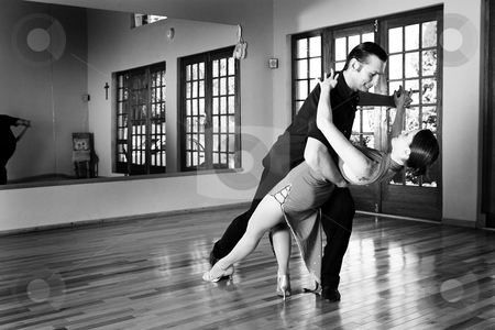 Two ballroom dancers practicing in their studio stock photo, A young adult couple dancing and practicing ballroom dancing together in a studio - Focus on woman - Black and white, high key effect by Sean Nel