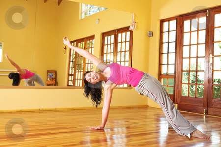 Healthy young woman in gym outfit stretching stock photo, Healthy young woman with dark hair exercising in studio. Yoga stretches associated with health and wellness, as well as general fitness and dieting. by Sean Nel