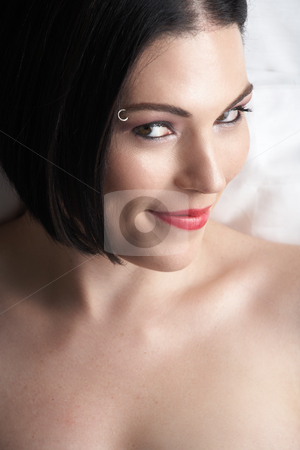 Nude adult woman stock photo, Sensual naked young Black haired adult Caucasian woman, wrapped in a charcoal colored satin, silk sheet on a bed in her bedroom. High contrast lighting, focus on Lips by Sean Nel