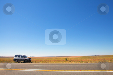 Car next to the road stock photo, SUV parked next to the road on an open stretch of highway with very little on the landscape. Blue sky provides copy space. by Sean Nel