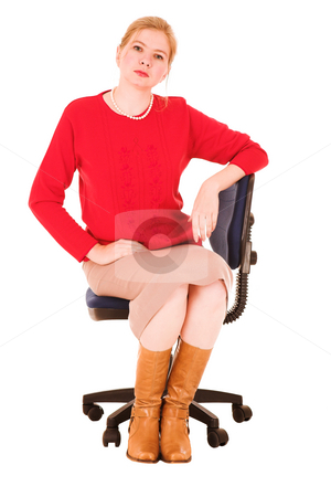 Businesswoman in red sitting on chair stock photo, Blond adult businesswoman in red pullover and brown boots. Isolated on white. Woman is upset and very serious by Sean Nel