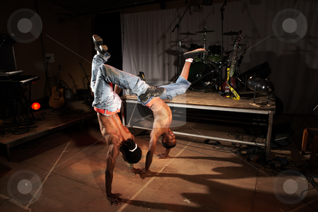 Two hip-hop dancers stock photo, Two freestyle hip-hop dancers in a dancing training session. Two young adult males in a home training studio with stage and instruments. Lit with spotlights. Movement on edges of dancers by Sean Nel