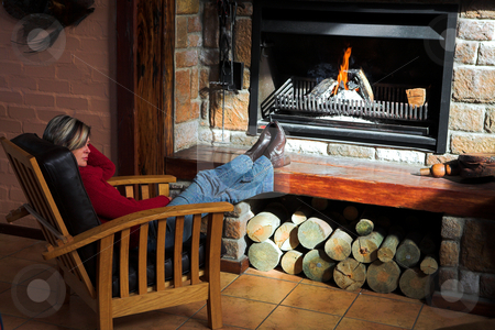 Beautiful adult woman sitting in front of the fire stock photo, Beautiful adult woman with short hair sitting on a comfortable leather chair in front of the fire by Sean Nel