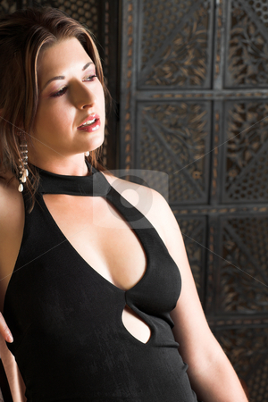 Sexy adult woman stock photo, Beautiful young sexy adult brunette woman with long auburn hair, in formal black dress on a wooden textured background by Sean Nel