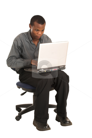 Businessman #158 stock photo, Businessman in a grey shirt, sitting on an office chair, working on a laptop. by Sean Nel