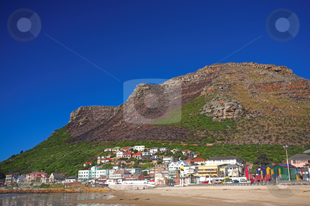 The colorful town of Muizenberg next to the sea stock photo, The colorful town of Muizenberg against the mountain next to the ocean, Western Cape, South Africa. A beach in the foreground and large mountain in the background. The image was shot with polarizing filters so the mountain looks almost cut out from the sky. by Sean Nel