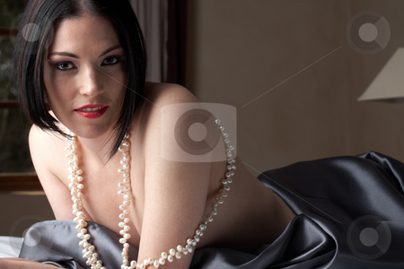Sexy brunette woman stock photo, Sexy young brunette caucasian woman wrapped in dark silk and pearls lying  on a bed by Sean Nel