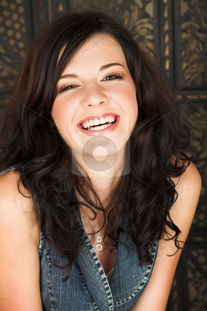 Young brunette woman stock photo, Young adult brunette woman with a white top and long brown curly hair and brown eyes looking at the camera and laughing by Sean Nel