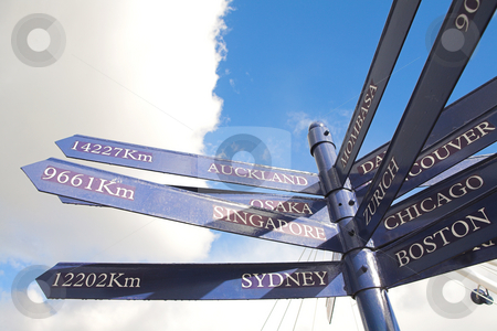 Distance marker to various cities stock photo, A blue distance marker against a cloudy blue sky for the various cities in the world (in km) by Sean Nel