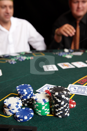 Card gambling stock photo, Stacked Poker Chips. People playing cards, chips and players gambling around a green felt poker table. Shallow Depth of field by Sean Nel