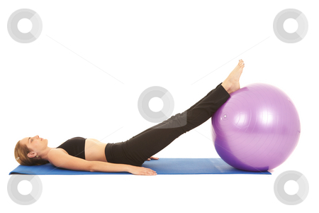 Pilates exercise series stock photo, Fit young brunette pilates instructor showing different exercises on a white background with basic pilates equipment including a ball and yoga mat. White background, not isolated by Sean Nel