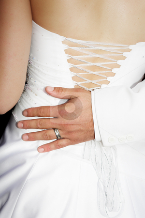 Bridegrooms hand on the back of his bride stock photo, The hand of a new groom on the back of his new bride. The couple is dressed in matching white wedding outfits and her dress is laced up and studded with embroidered crystals. by Sean Nel