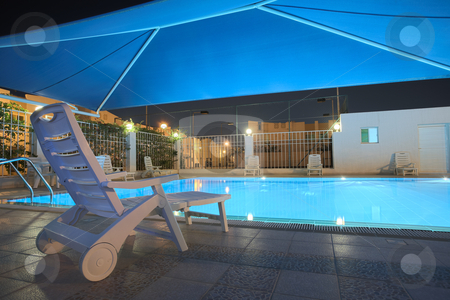 Swimming pool at night stock photo, Blue water in a clean swimming pool at night. The pool is covered with a blue shade net roof ? HDR type image by Sean Nel