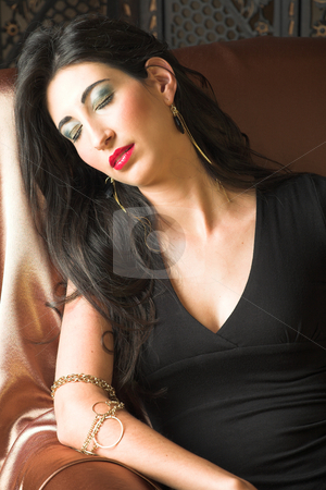 Italian adult woman stock photo, Beautiful young sexy adult Italian woman with long black hair, in formal black dress on a textured wooden background, sleeping on a luxurious couch ? Hard light, high key by Sean Nel
