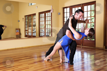 Two ballroom dancers practicing in their studio stock photo, A young adult couple dancing and practicing ballroom dancing together in a studio - Focus on woman by Sean Nel