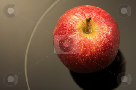 Fresh red apple stock photo, Fresh red apple with drops of water on a black glass backdrop by Sean Nel