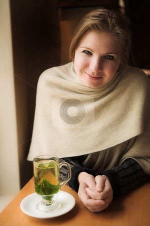 Blonde woman with mint tea stock photo, Blonde woman with hot mint tea next to a natural light window in the beginning of winter. Shallow Depth of Field by Sean Nel