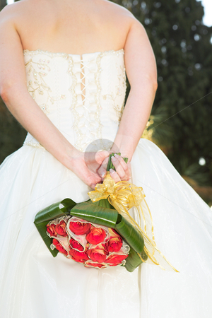 Young bride with flowers stock photo, Young new bride in a silk wedding gown holding a bouquet of red roses behind her back by Sean Nel