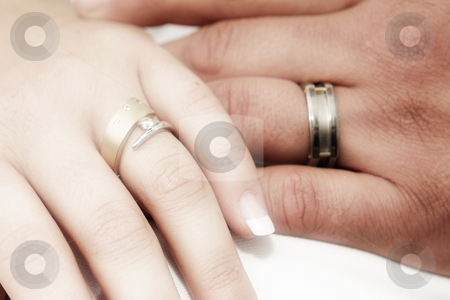 Romantic hands with wedding rings stock photo, Romantic image of the wedding rings of a new young adult couple on their wedding day. The image is in a soft focus romantic effect, with the focus on the fingers of the hand of the woman by Sean Nel