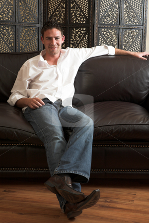 Relaxed young man stock photo, Relaxed young adult male wearing blue jeans, a loose white cotton shirt and sitting comfortable on a leather couch by Sean Nel