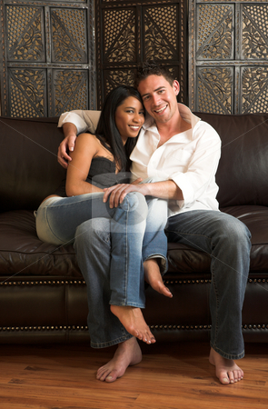 Intimate lovers embrace stock photo, Loving couple on a brown leather couch by Sean Nel