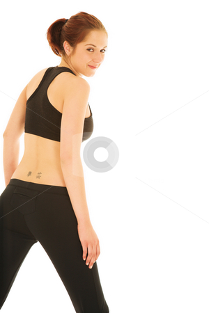 Sexy redhead woman in gym clothes stock photo, Sexy young adult woman in black gym outfit isolated on white. Her back is turned to the viewer, and she is smiling by Sean Nel