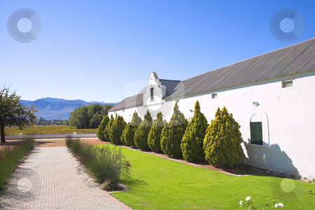 Old winery and walkway stock photo, Original winery on the Wine farm of Plaisir de Merle, South Africa, on a sunny summers day. Path leads to the vineyards. Example of old Cape Dutch Architecture by Sean Nel