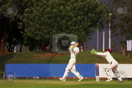 Cricket player hitting ball stock photo, Cricketers playing in the late afternoon, Batsman hitting ball, wicketkeeper trying to catch by Sean Nel
