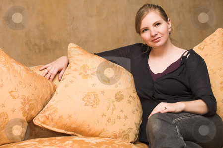 Blonde adult woman stock photo, Young blonde adult woman with green eyes sitting on a luxurious orange couch by Sean Nel