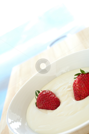 Breakfast yogurt with strawberries stock photo, Fresh red strawberries and thick dairy yogurt for breakfast in a white bowl on a kitchen table by Sean Nel