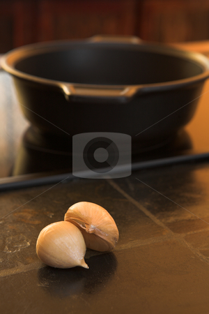 Cloves of garlic lying on a kitchen counter stock photo, Two cloves of garlic lying on a black stone kitchen counter with a steel pot in the background  by Sean Nel