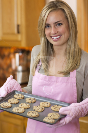 Attractive Blond Woman Baking Chocolate Chip Cookies stock photo, A young woman is holding a baking sheet of cookies and smiling at the camera.  Vertically framed shot. by Edward Bock
