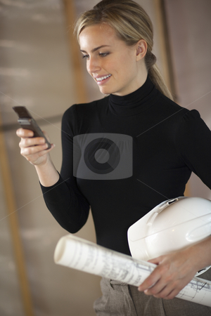 Woman With Blueprints, Hardhat, and Cell Phone stock photo, A young woman is holding a cell phone, a hardhat, and blueprints.  She is smiling and looking at the phone.  Vertically framed shot. by Edward Bock