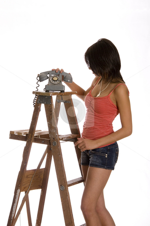 Picking up phone stock photo, Teenage girl standing on ladder about the anwser phone by Yann Poirier