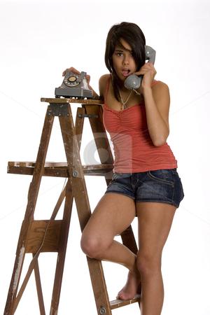 Surprise on the phone stock photo, Teenage girl standing barefoot on ladder talking on a old rotary phone with a surprise expression by Yann Poirier